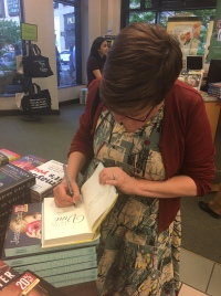 Marla signing a copy of Dying at the Vine at Barnes and Noble.